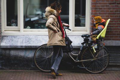 Mutter mit Fahrrad und Kind im Kindersitz
