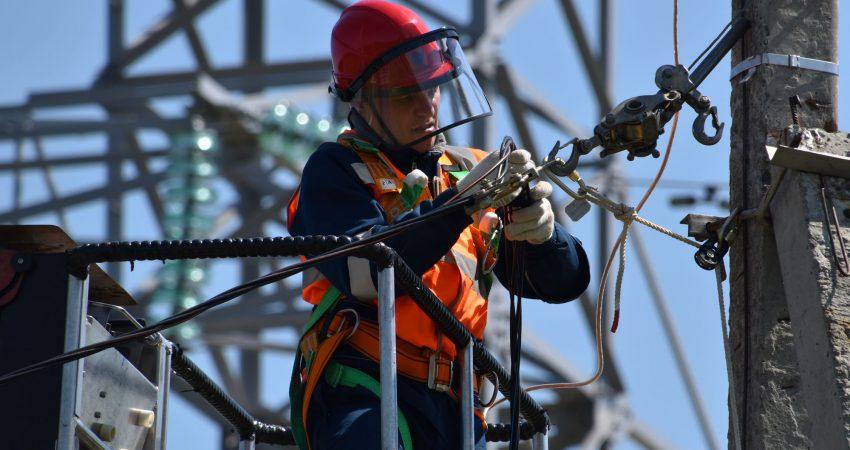 Ein Techniker arbeitet an einer Stromleitung
