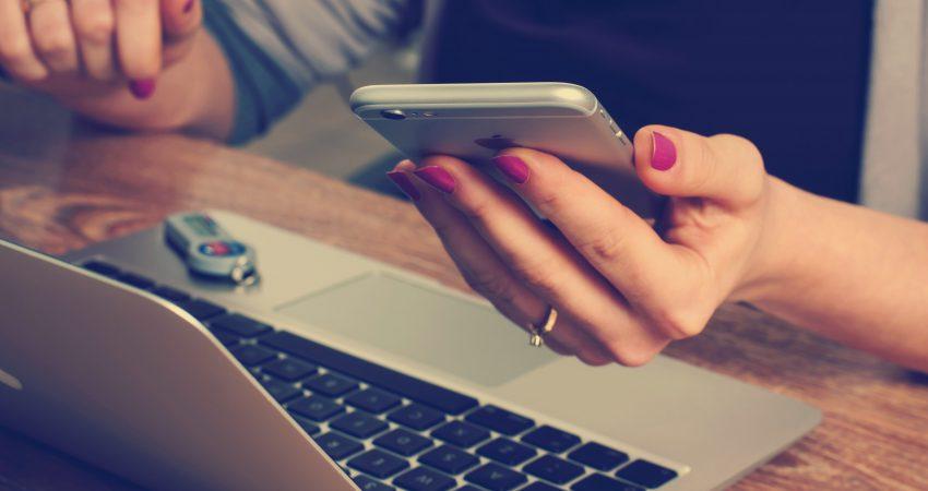 eine Frau vor einem Laptop mit einem Mobiltelefon in der Hand