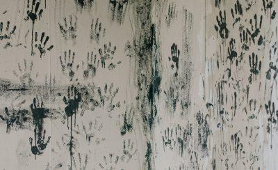 Schwarze Handabdrücke auf grauer Wand