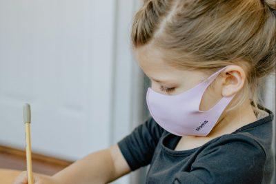 Mädchen mit rosa Maske sitzt am Tisch und schreibt mit Bleistift