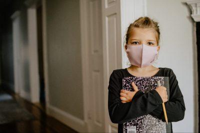 Mädchen mit rosa Mundschutz lehnt an Tür und drückt Buch und Bleistift an sich