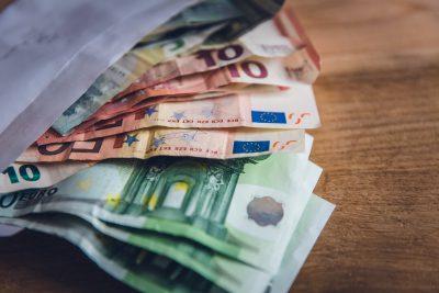 aus einem Umschlag schauen einige Euro-Banknoten heraus