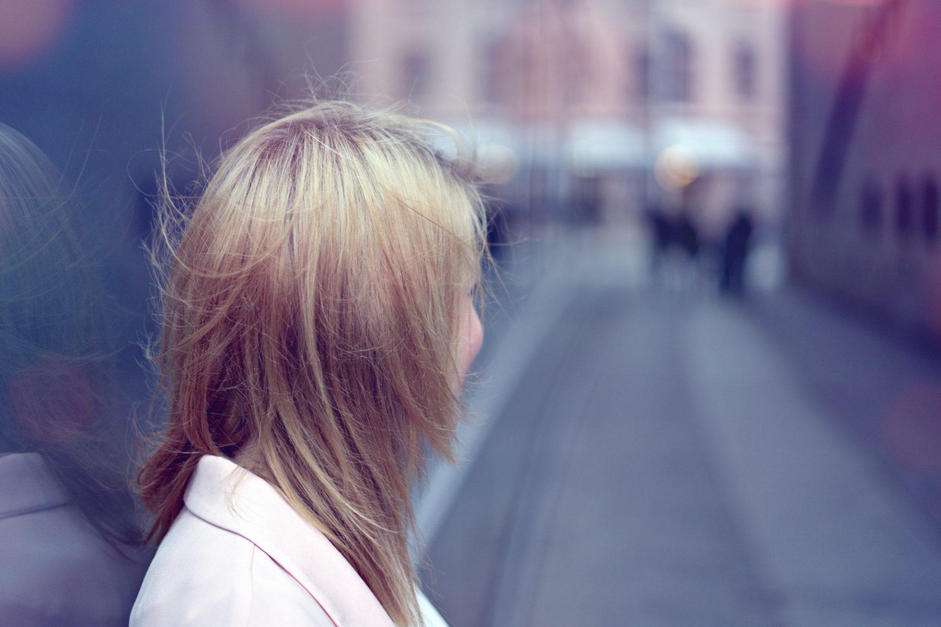 Junge, blonde Frau, die in Straßenschlucht blickt