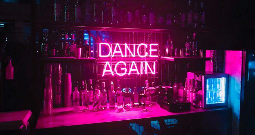 """Bar mit pinker Leuchtschrift """"Dance again"""""""