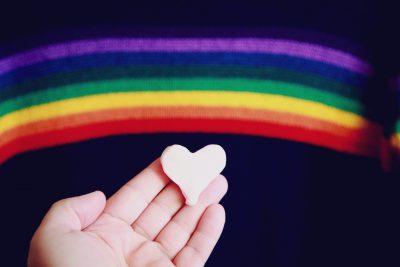 Regenbogenflagge im Hintergrund, im Vordergrund eine Hand mit Herz aus Marzipan