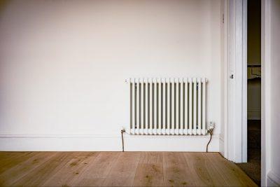 Heizung vor einer weißen Wand und auf Holzfußboden