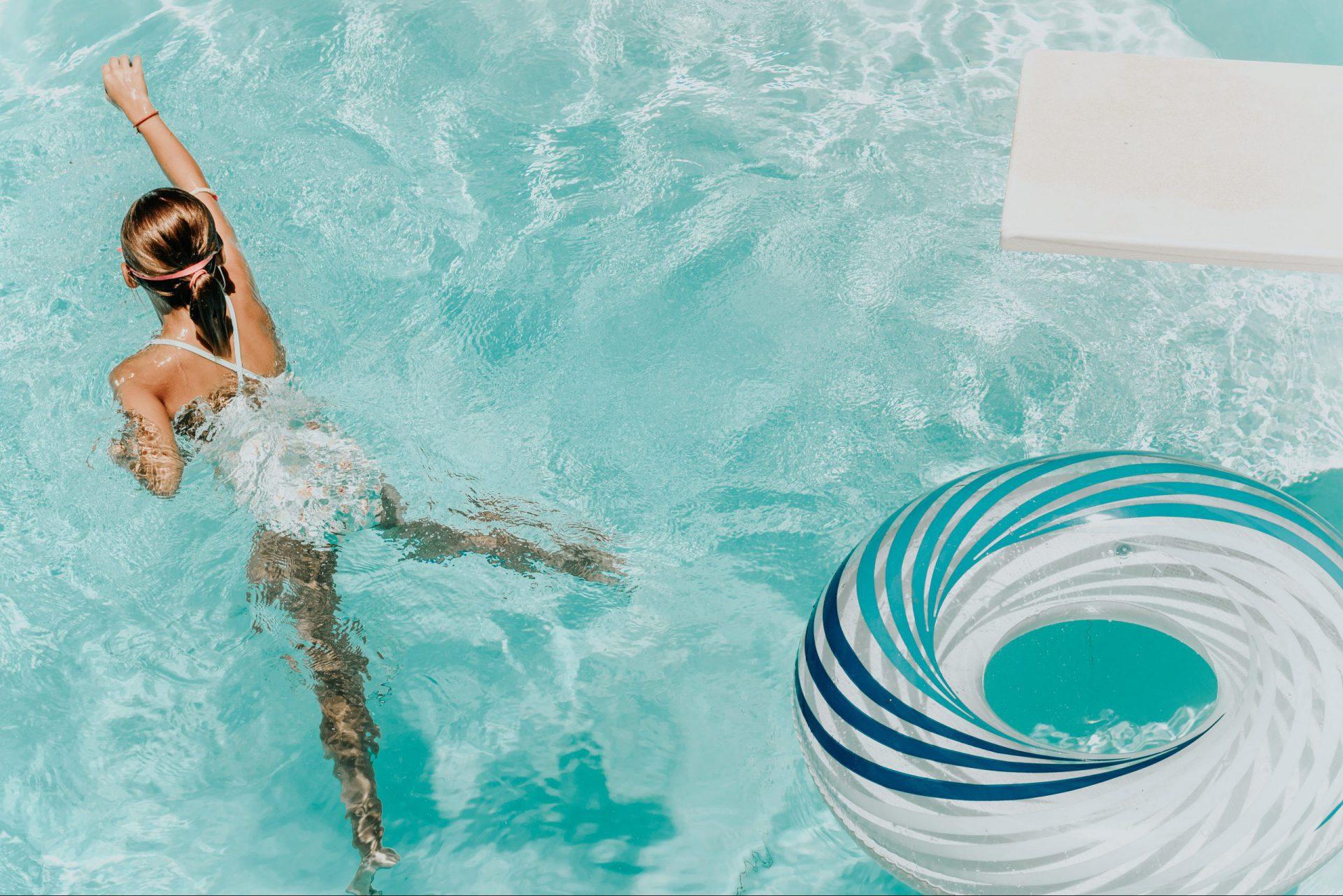 Mädchen im Schwimmbecken, das von Schwimmreifen wegschwimmt