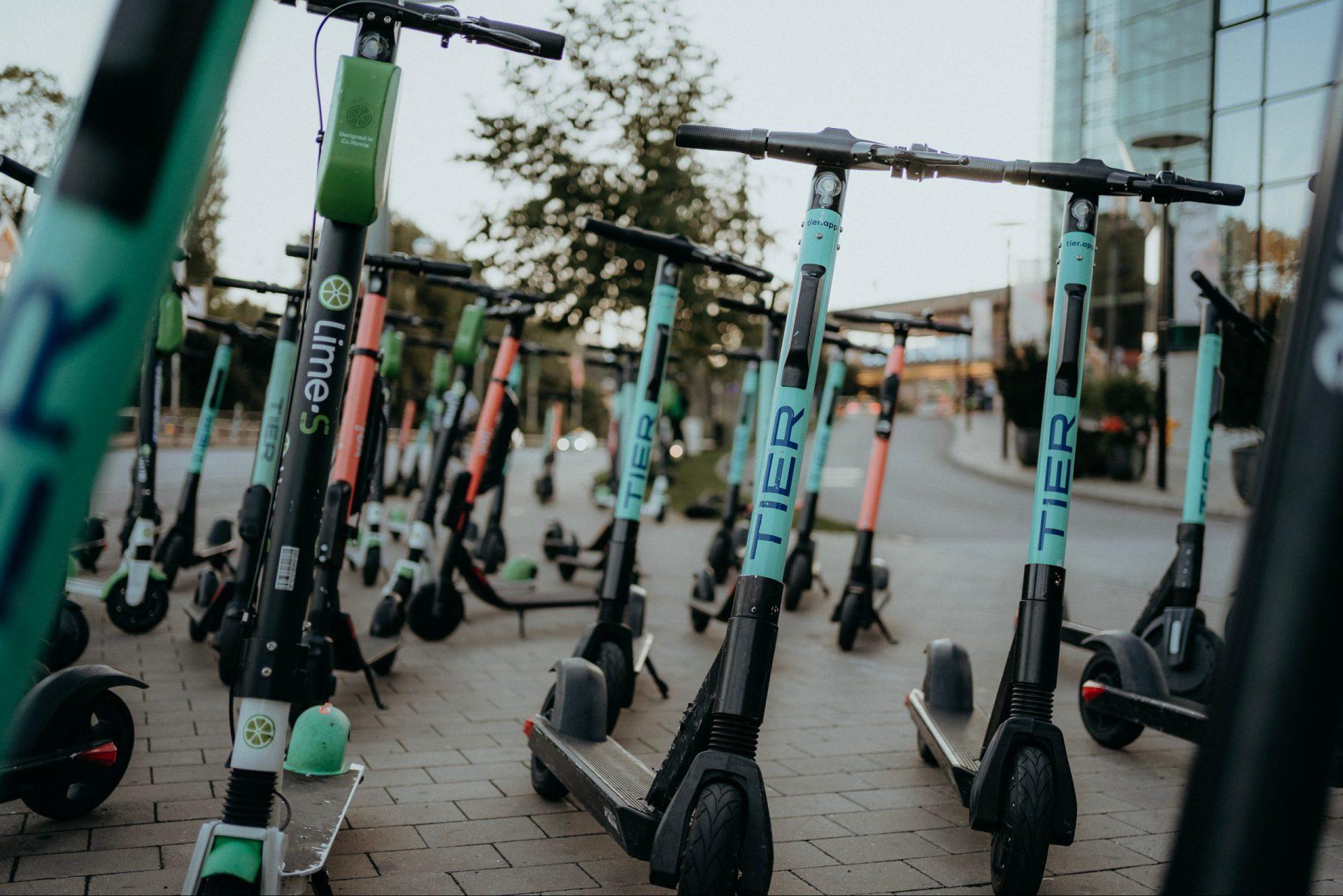 E-Scooter verschiedener Hersteller auf einem Parkplatz