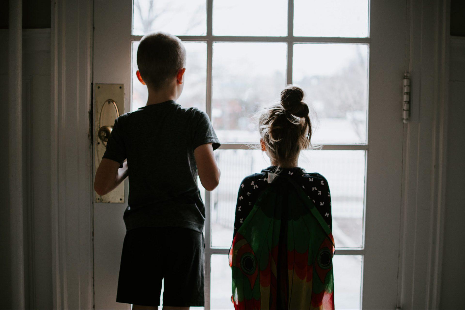 Rückenansicht eines Jungen und eines Mädchens, die vor einer verschlossenen Terrassentür stehen