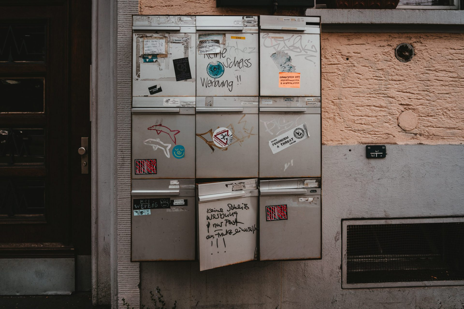 Briefkastenblock mit 9 Briefkästen, die Aufkleber und Schmierereien tragen