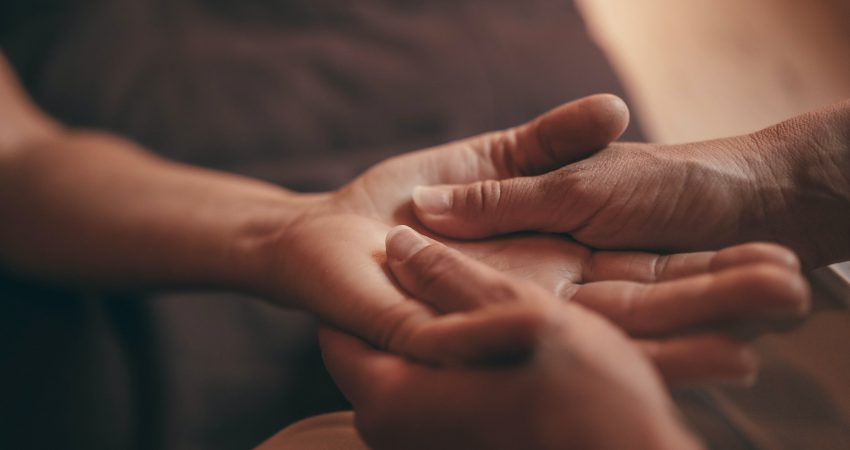 Jemand massiert einem anderen die Hand