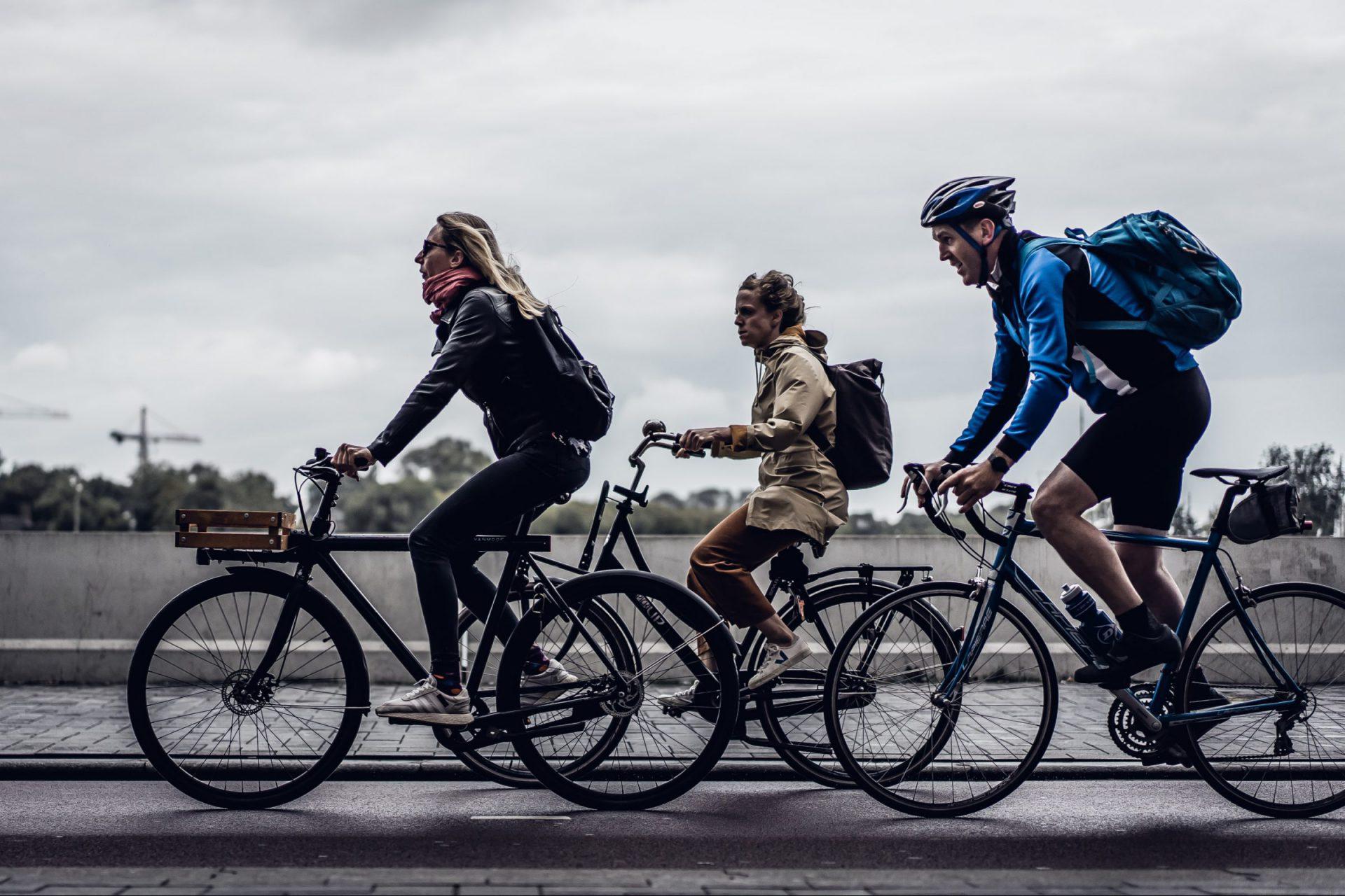 Drei Fahrradfahrer*innen, die über eine Brücke fahren