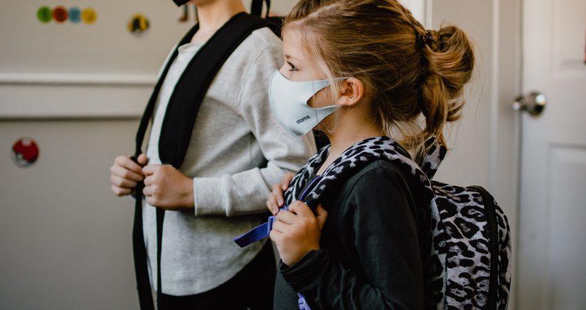 Stehender Junge und stehendes Mädchen mit Masken und Rucksack