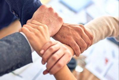 Vier Hände, die ineinander greifen